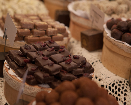 Asorted chocolate truffles and pralines. Chocolate and coconut candies on the counter in the confectionery store. Banco de Imagens