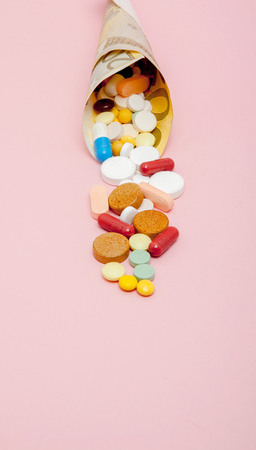 Medical pills and tablets in euro bank notes money as a symbol of health care costs. Concept of medicine, money and health