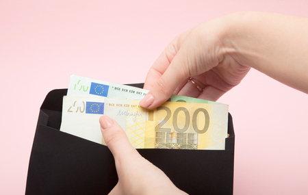 Women hands put euro in black envelope on pink background.