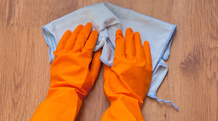 A woman hands Using blue rags wipe the wooden floor.