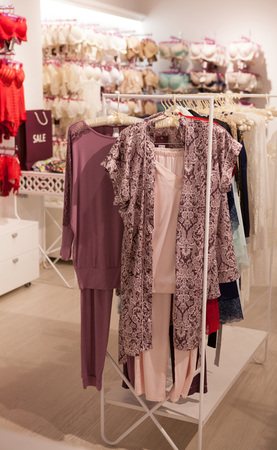 Silk lingerie hanging on a rack on showroom. Collection of sensual underwear, tops, shorts and nightdresses. Imagens