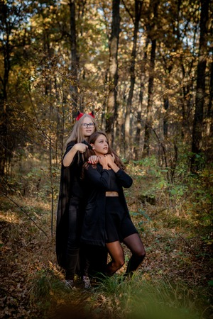 Halloween daemon kills the witch in the woods. Teenagers in Halloween costumes in the woods.