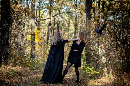 Halloween demon and witch in the woods.