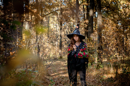 Halloween witch with a knife in the woods.