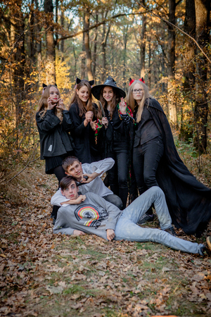 Teenagers in Halloween costumes in the woods.