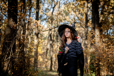 Halloween witch with a knife in the woods. Archivio Fotografico - 110453588