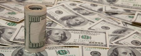 stack of dollars against the backdrop of money