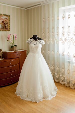 an elegant wedding dress on a mannequin in a beautiful light room. Imagens