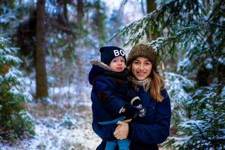 mother keeps a small child in her arms. A walk in the snowy winter park. Imagens