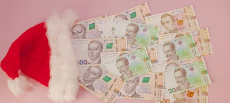 Ukrainian hryvnia banknotes coming out of Santa Claus hat on a pink background. Christmas Shopping Concept. Stock Photo