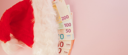 Euro banknotes coming out of Santa Claus hat on a pink background. Christmas Shopping Concept.