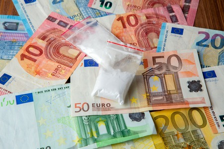 packets of drugs against the background of the euro.