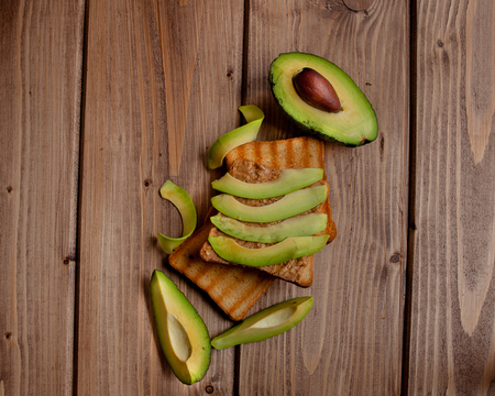 Avocados and toasters with peanut paste on a wooden background. Homemade delicious and healthy breakfast toast. Stock Photo