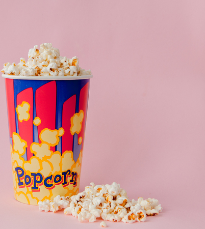 Popcorn on a pastel pink background and a place for text. Flat lay. Copyspace. Cinema Concept. Background.