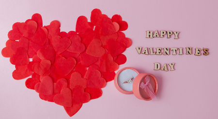 A great heart of small paper hearts and a wedding ring on a pink background with an inscription Happy Valentine's Day.