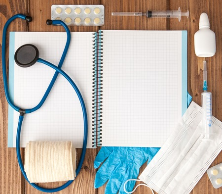 Syringe, stethoscope, blank page notepad, bandage, pill, elastic bandage and gloves on the doctor table. Medical diagnosis or doctor prescription mockup.