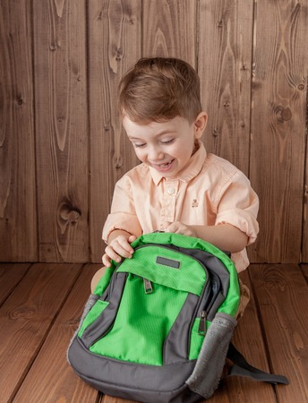 Little boy with large school bag on wooden background
