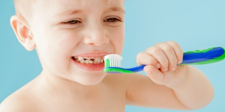 Portrait of little boy with toothbrush on blue background.