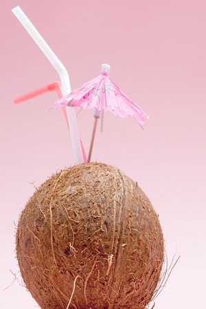 Coconut with drinking straw and umbrella on pink background with copy space.
