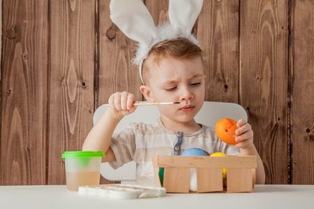 Little boy painting colorful eggs for easter on wooden background.