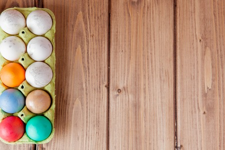 Colorful Easter eggs in box on wooden background with copy space. Stok Fotoğraf
