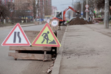 Road signs, detour, road repair on street background, truck and excavator digging hole. Standard-Bild