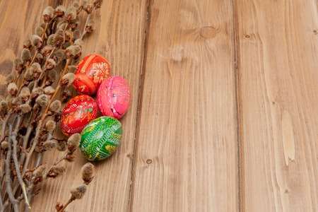 Still life with Pysanka, decorated Easter eggs, dry willow branches on black wooden background, top view, copy space.