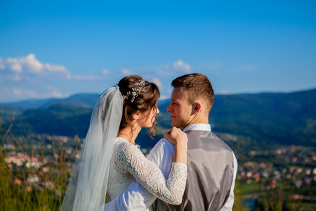 Newlyweds smile and hug each other among the meadow on top of the mountain. Wedding walk in the woods in the mountains, the gentle emotions of the couple, photo for Valentines Day. Imagens