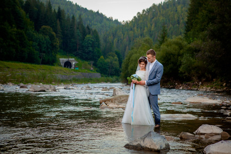 Happy newlyweds standing and smiling on the river . Honeymooners, photo for Valentine's Day. Stock Photo