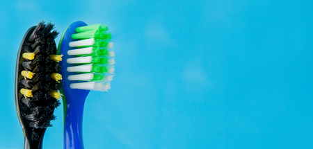 Set of toothbrushes in glass on blue background. Concept toothbrush selection, copy space. Foto de archivo