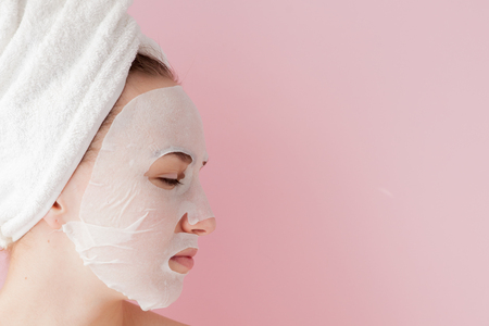 Beautiful young woman is applying a cosmetic tissue mask on a face on a pink background. Healthcare and beauty treatment and technology concept.