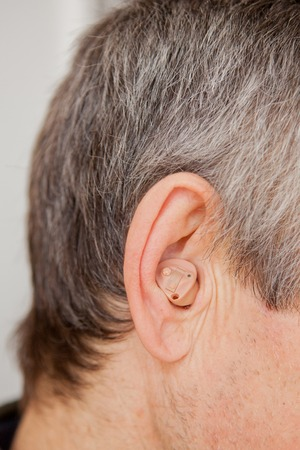 Close-up Digital modern hearing aid in the ear of aged old man. Reklamní fotografie
