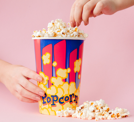 Hand takes a popcorn from a paper cup on a pink background. Woman eats popcorn.Cinema Concept. Flat lay. Copyspace.