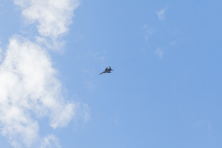 Military fighter in the blue sky with white clouds.