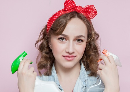 Beautiful young woman with pin-up make-up and hairstyle with cleaning tools on pink background. Stock Photo