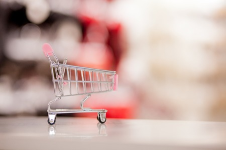 Empty shopping cart with abstract blur supermarket discount store aisle and product shelves interior defocused background.