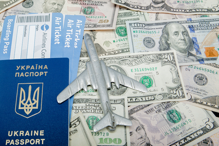 Airplane, passport and airline tickets against the background of dollars. Stockfoto