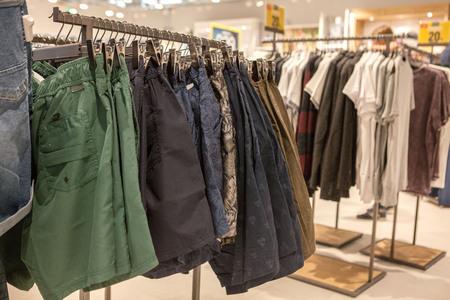 Shorts on the store shelf. Fashionable clothes on the shelves in the store. Shorts hanging on the vests in the fashion store. Showcase, sale, shopping. Stock Photo