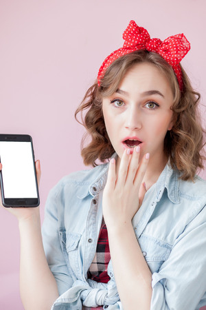 Beautiful young woman with pin-up make-up and hairstyle over pink background with mobile phone with copy space. 스톡 콘텐츠