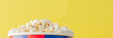 Popcorn in a red and white cardboard box on a yellow background. Copy space. Flat lay.