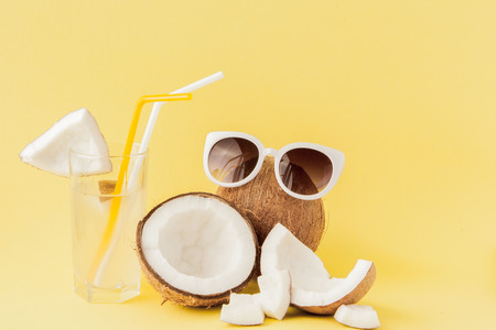 Fresh Coconut cocktail with a straws on yellow background, copy space. 写真素材