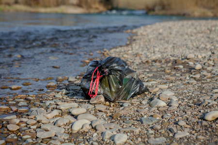 River pollution near the shore, garbage pack near the river, plastic food waste, contributing to pollution. Banco de Imagens