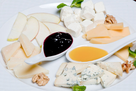 Cheese plate on a black table. Many kinds of cheese - a plate