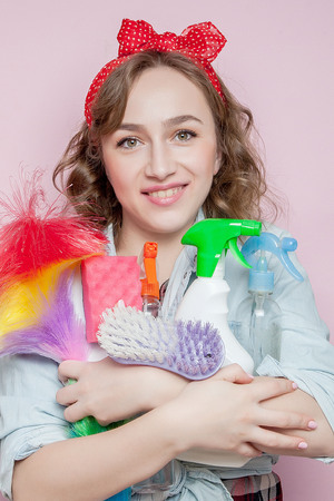 Beautiful young woman with pin-up make-up and hairstyle with cleaning tools on pink background. Standard-Bild