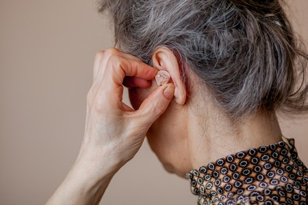 closeup senior woman inserting hearing aid in her ears. Stock Photo