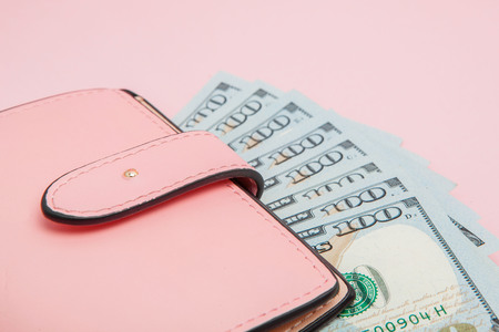 Purse with one hundred dollars banknotes on pink background. Flat lay, top view, copy space.