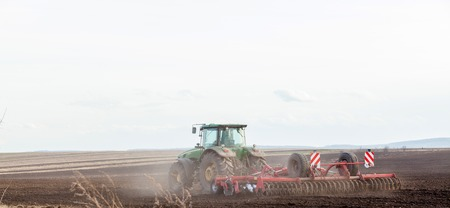 Agriculture,tractor preparing land with seedbed cultivator as part of pre seeding activities in early spring season of agricultural works at farmlands.
