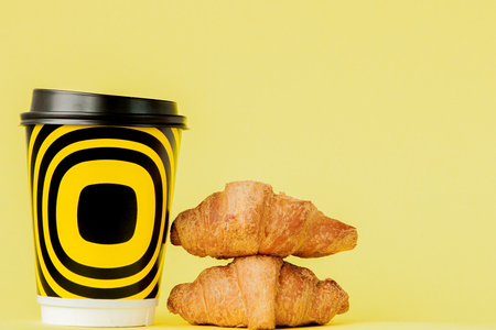 Paper cup of coffee and croissants on a yellow background, Copy space. Foto de archivo