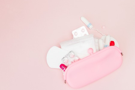 Women intimate hygiene products - sanitary pads and tampons on pink background, copy space. Menstrual period concept. Top view, flat lay, copy space.