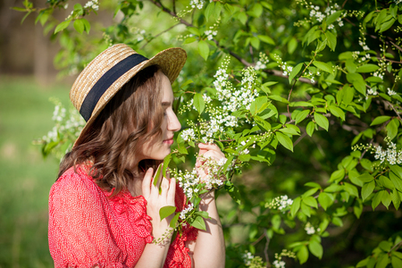Young girl blowing nose and sneezing in tissue in front of blooming tree. Seasonal allergens affecting people. Beautiful lady has rhinitis